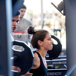Profile of determined young woman lifting weights at the TCU rec center