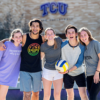 Five TCU students form a happy huddle on the sand volleyball court outside the rec center