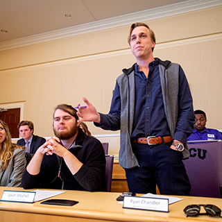 A male student stands to speak at a TCU student government meeting in the chambers of the student union.