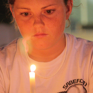 Close up of female TCU student looking thoughtful as she holds a candle before her face.
