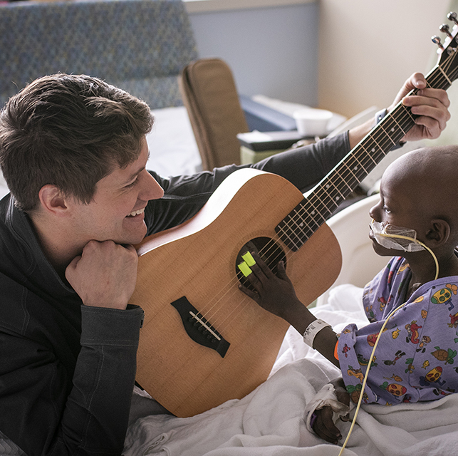 J. Mack Slaughter '09 plays music with a young patient
