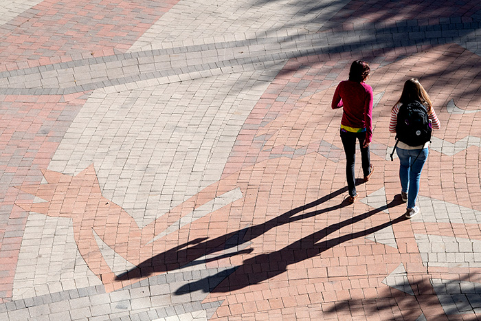 Two students walking through the Campus Commons